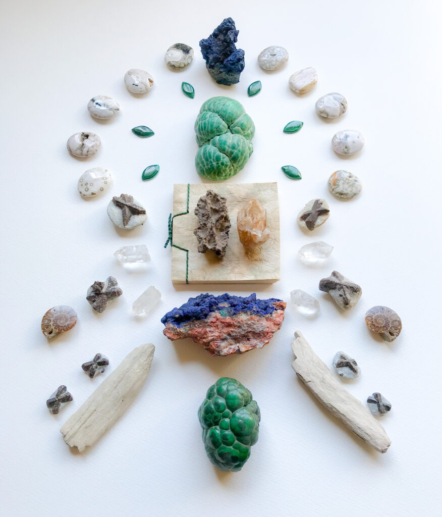 Fulgurite, Elestial Fenster Quartz upon a book of natural handmade paper, Quartz, Azurite on matrix, Stuarolite, Malachite, Azurite, Petrified Wood, Ammonite, and Ocean Jasper